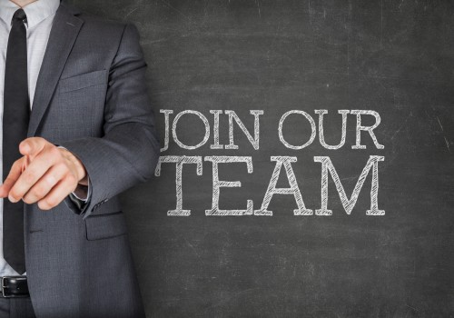 Join our team on blackboard with businessman finger pointing